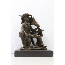 Bronze Cowboy seated with...